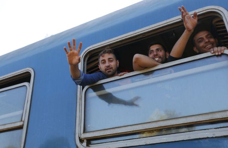 Migranten zwaaien vanuit een trein die richting Oostenrijk gaat vanuit Röszke, Hongarije. Beeld reuters
