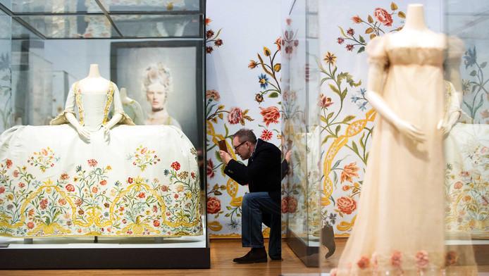 Een bezoeker bekijkt jurken tijdens de perspreview Catwalk.