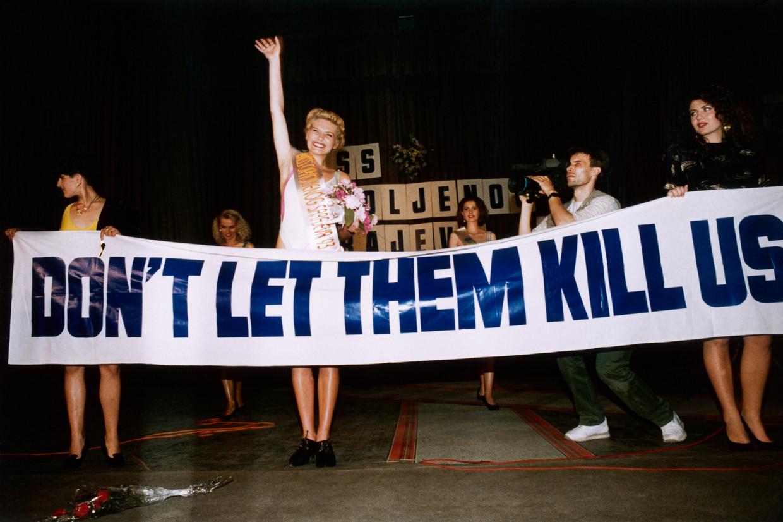 De wereldberoemde foto van Inela Nogić als winnaar van de missverkiezing in belegerd Sarajevo en het spandoek met de tekst 'Don't let them kill us'.  Beeld Patrick Robert / Getty