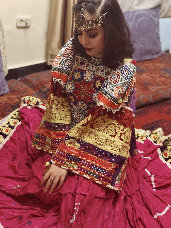 Een vrouw gekleed in kleurrijke traditionele Afghaanse klederdracht.