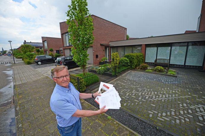 Theo Kupper toont de papieren die bewijzen dat er een haag bij de voortuin moet staan. Zijn buren hebben die verwijderd om een oprit aan te leggen waar ze hun camper kunnen neerzetten.
