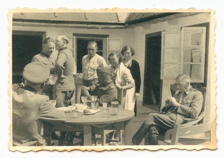 Deel van de kampstaf, aperitievend voor de kantine in het Vorlager , met vermoedelijk geroofde kristallen glazen.  Op een steenworp afstand lagen de gaskamers. Johann Niemann is de derde van links. Beeld United States Holocaust Memorial Museum