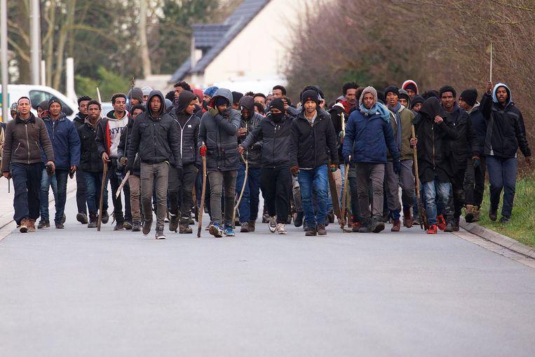 Migranten tijdens de rellen in Calais gisteren. Beeld EPA