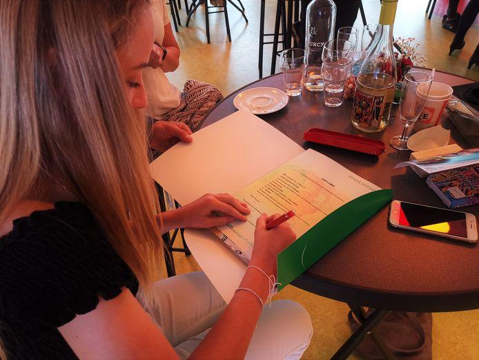 Daniek Vervoort tekent op haar laatste schooldag op Metameer haar diploma.