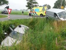 Auto eindigt in sloot na botsing met busje bij spoorwegovergang Staphorst: twee gewonden