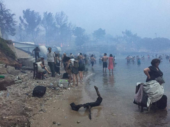 Mensen vluchten het water in bij het strand van Argyris Akti, Nea Makri, Griekenland.