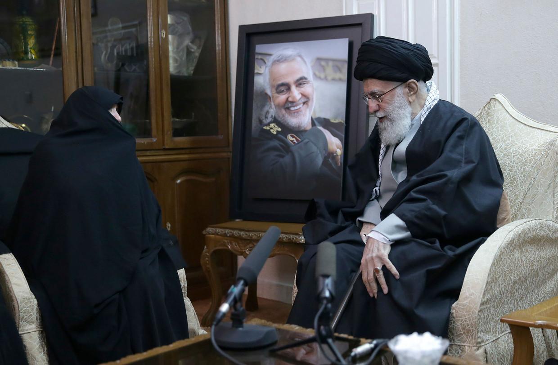 De Iraanse leider ayatollah Ali Khamenei met een portret van de gedode generaal Soleimani, met een familielid van de generaal. Beeld AP