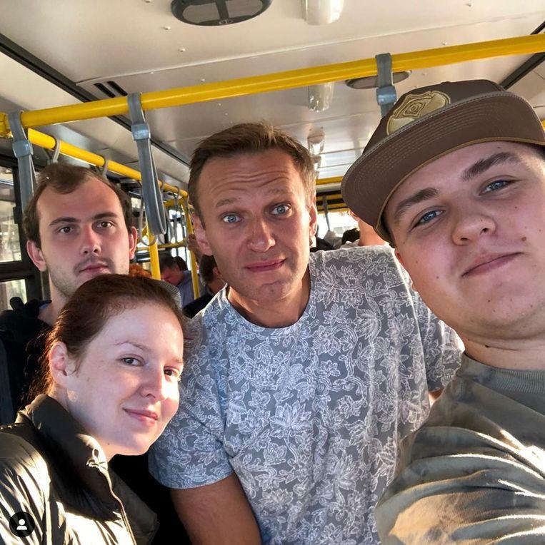 Navalny in de bus op weg naar het vliegveld, waar hij in het vliegtuig onwel zou worden. Beeld AP