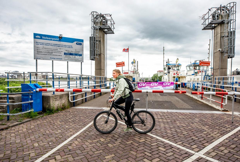 Studente Tessa Volkers staat met haar fiets voor een dichte pont in verband met de landelijke ov staking.  'Ik duik weer lekker mijn bed in.' Beeld Raymond Rutting / de Volkskrant