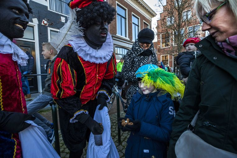 Toeschouwers krijgen snoepgoed van Zwarte Pieten tijdens de intocht van Sinterklaas in Dokkum vorig jaar.  Beeld ANP