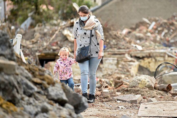 Een vrouw en een kindje lopen door het puin dat na de overstromingen in Pepinster is achtergebleven.