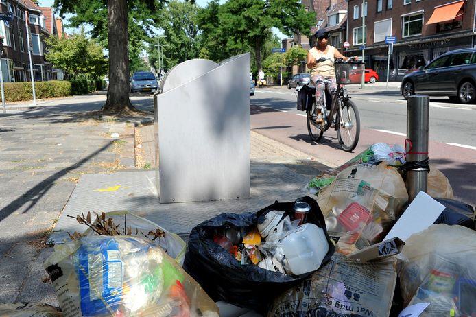 Voorbeeld van het verkeerd aanbieden van huisvuil. In dit geval ligt de vuilniszak met restafval naast de container. Handhavers spitten de zak soms door op zoek naar identiteitsgegevens van de persoon die het vuil heeft gedumpt.