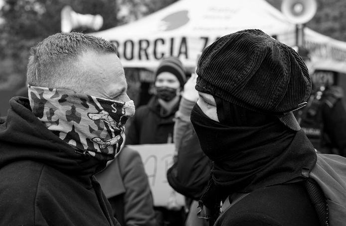 Een demonstrant (rechts) en tegendemonstraten (link) staan tegenover elkaar tijdens de Poolse protestbewegingen.