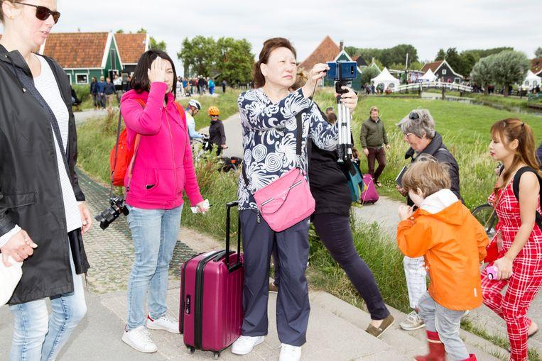 Chinese toeristen op de Zaanse Schans. Amsterdam spreidt het toerisme graag uit over de regio. Beeld Sanne Zurné