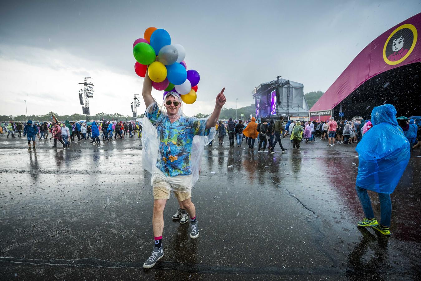Festivalgangers tijdens een regenbui op de laatste dag van het muziekfestival Pinkpop.