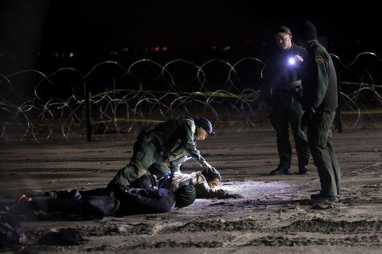 Drie Hondurezen worden door de politie opgepakt nadat ze te voet nabij Tijuana de Amerikaanse grens zijn overgestoken. Beeld AP