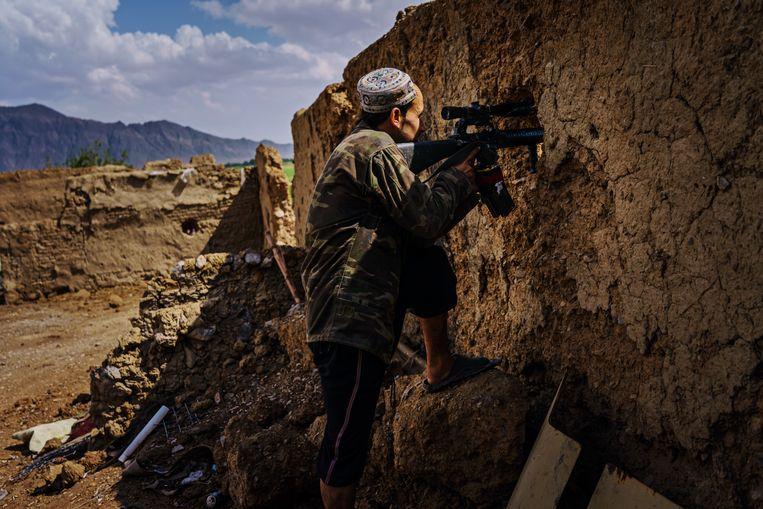 Een schutter van de nationale veiligheidstroepen houdt in mei nog de omgeving in Panjwayi onder schot. Ruim een maand later, begin juli, zal dit district in de provincie Kandahar in handen van de Taliban vallen. Beeld Los Angeles Times via Getty Images