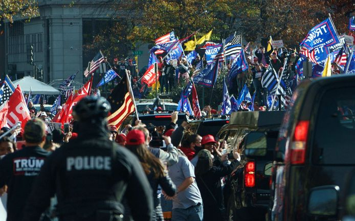 De betogers juichen als de autocolonne van de president voorbij rijdt.