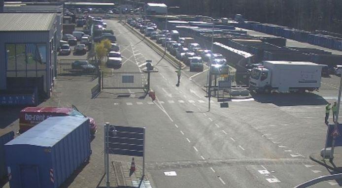 Achter in beeld de file voor de milieustraat in Tilburg. De gemeente roept op de webcambeelden te bekijken voor je je afval komt brengen.