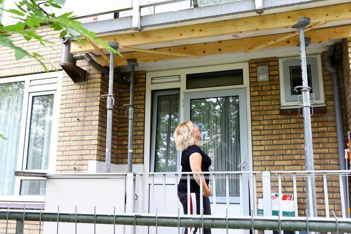 Een bewoonster op haar balkon aan de Maasstraat. Al maanden worden deze balkons ondersteund met stempels.