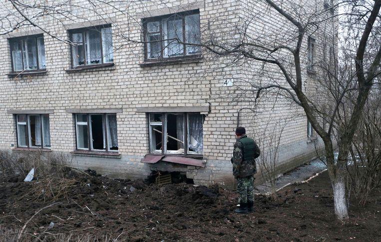 Een soldaat kijkt naar een beschadigd schoolgebouw in Artemivsk in Oekraïne.