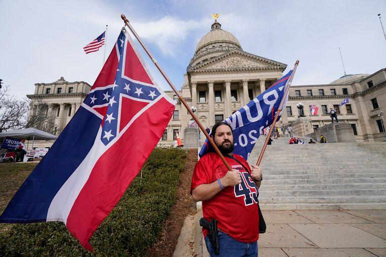 Deze demonstrant voert de oude vlag van Mississippi mee, die symbool staat voor burgeroorlog en slavernij.  Beeld AP