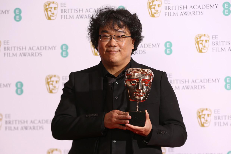 Director Bong Joon-ho met een prijs die hij op de BAFTA's kreeg in Londen, vorige week.   Beeld Joel C Ryan/Invision/AP