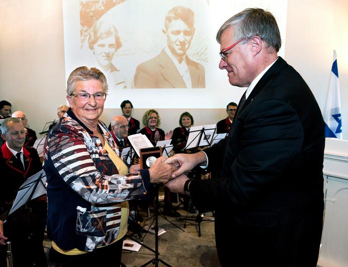 De ambasadeur van Israel Noar Gilon reikt een certificaat en medaille uit aan Wil Vernet - van Elk, de dochter van de Woerdense verzetsheld Jan van Elk.