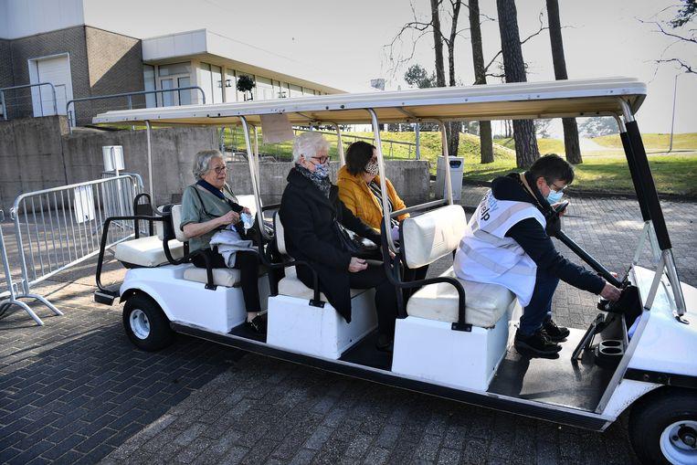 Ouderen laten zich vaccineren tegen covid-19 op Papendal. Na vaccinatie worden ze met een golfkarretje weer naar hun auto gebracht.  Beeld Marcel van den Bergh