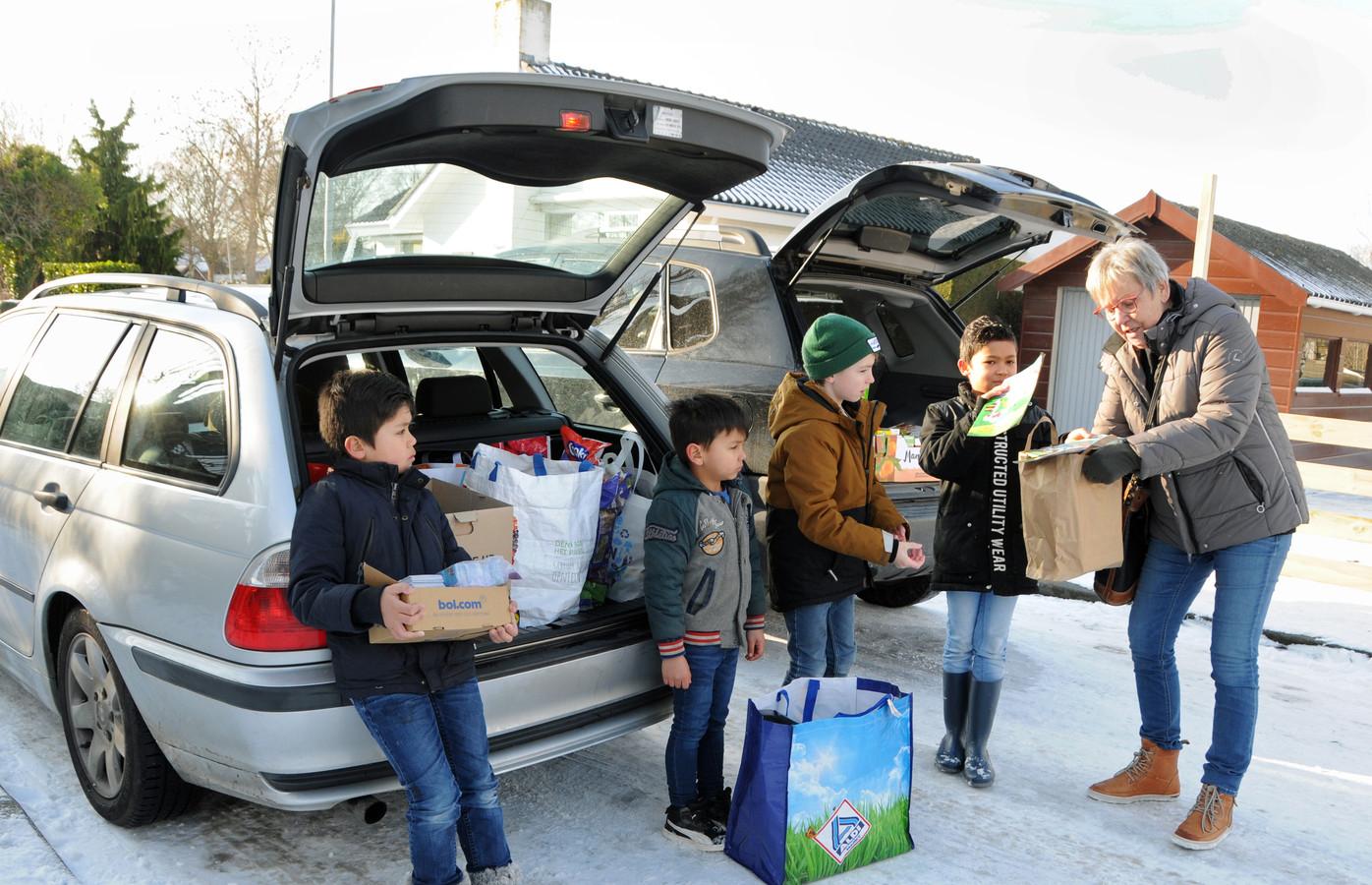 Vlnr: Ryan, Joël, Bowi en Calvin overhandigen twee kofferbakken vol spullen aan Ria Schoof. Zij nam de spullen namens de Voedselbank Schouwen-Duiveland in ontvangst