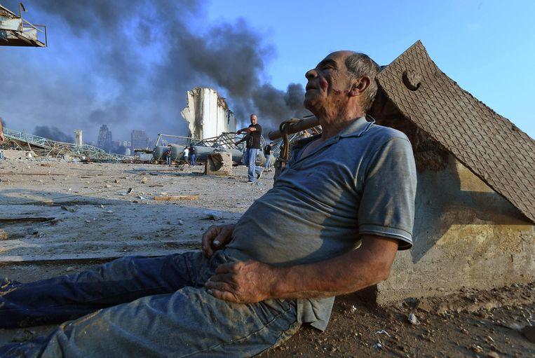 Een gewonde man wacht op medische hulp. Beeld AFP