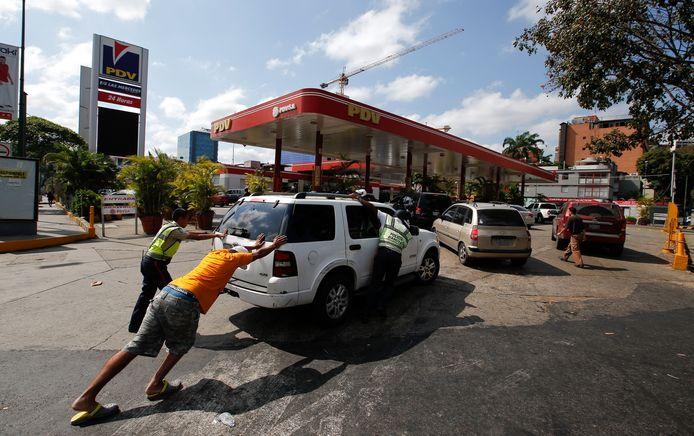 Venezolanen duwen een auto naar een van de weinige benzinestations in de hoofdstad Caracas die een eigen stroomvoorziening heeft.