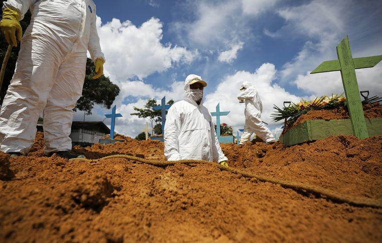 Grafdelvers draaien overuren in Manaus. Beeld REUTERS