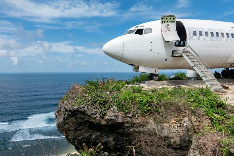Dit vliegtuig aan de Balinese westkust moet een toeristenattractie worden. Het is op het Indonesische eiland een soort traditie om afgedankte vliegtuigen te parkeren om er toeristen mee te lokken. Nu de toerismesector op het eiland lijdt onder coronamaatregelen, is de overheid scheutiger met planningsvergunningen voor zulke stunts.  Beeld EPA