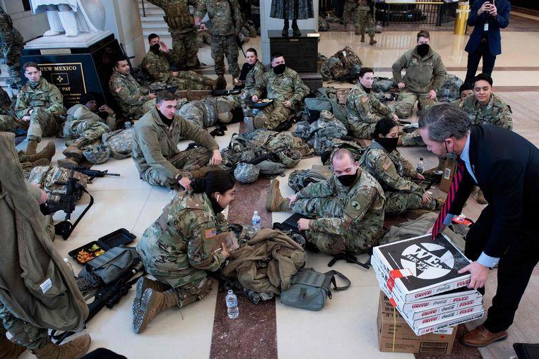 Leden van de Nationale Garde krijgen pizza aangeboden in het Capitool.  Beeld AFP