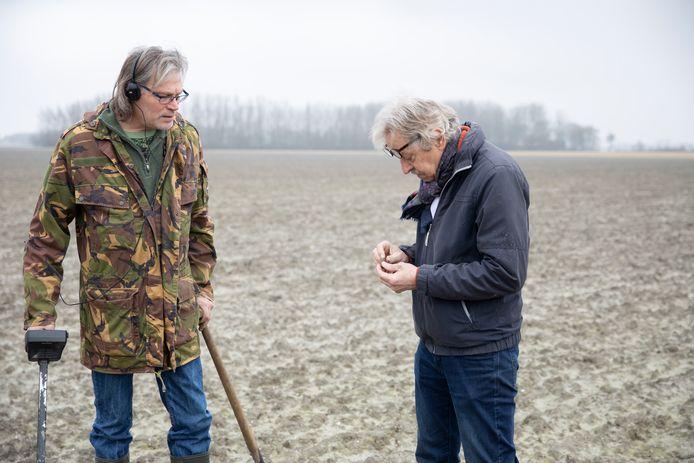 """Stef Nelisse (l) en Luitzen Bijlsma (r) bekijken de eerste vondst: een metalen huls. ,,Zeker niet van een landbouwvoertuig"""", weet akkerbouwer Adrie Romeijn van wiens zoon het land is."""
