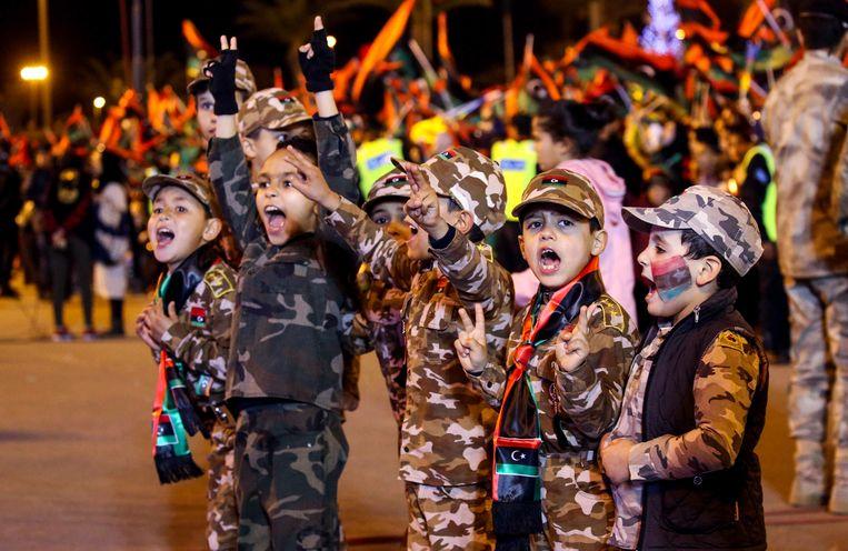 Libische kinderen in camouflage-uniformen nemen ook deel aan de festiviteiten.  Beeld AFP