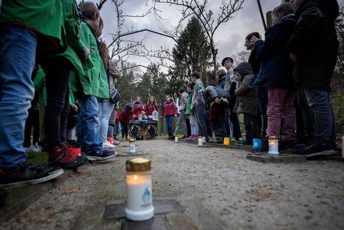 Ontsteken van het vredeslicht op de struikelstenen van de begraafplaats op landgoed De Grote Beek door scouts van de groep Johannes Vianney op 24 december 2019.