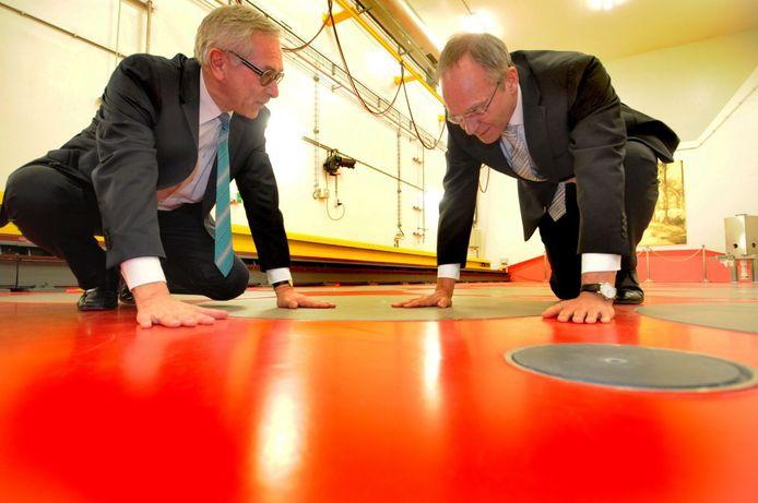 Directeur Hans Codée van de Covra en minister Henk Kamp (r) voelen de warmte die het hoogradioactief afval uitstraalt. foto Lex de Meester