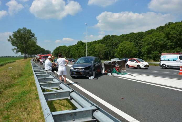 Op de A12 bij de afrit naar Nieuwebrug en Waarder is een aanhangwagen door een botsing op zijn kant terecht gekomen.