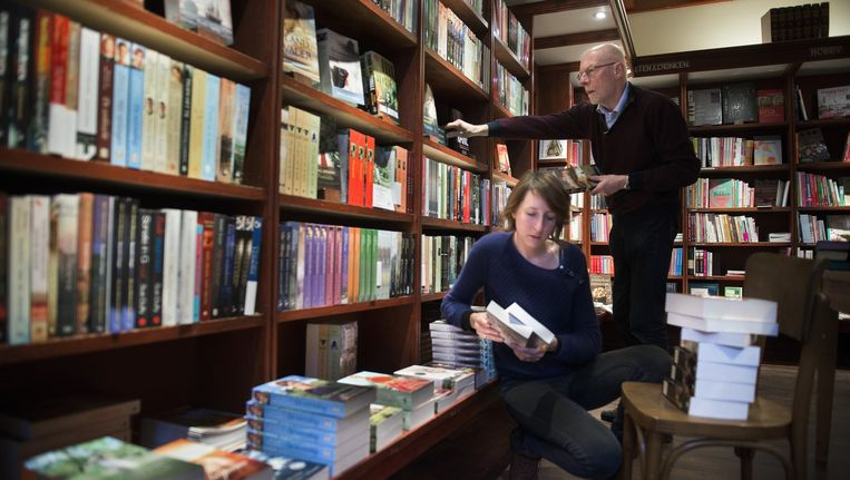 Boekverkoper Heerco Walinga en zijn dochter Elise Walinga bij de afdeling christelijke romans in zijn boekwinkel in Ermelo. Beeld Bram Petraeus