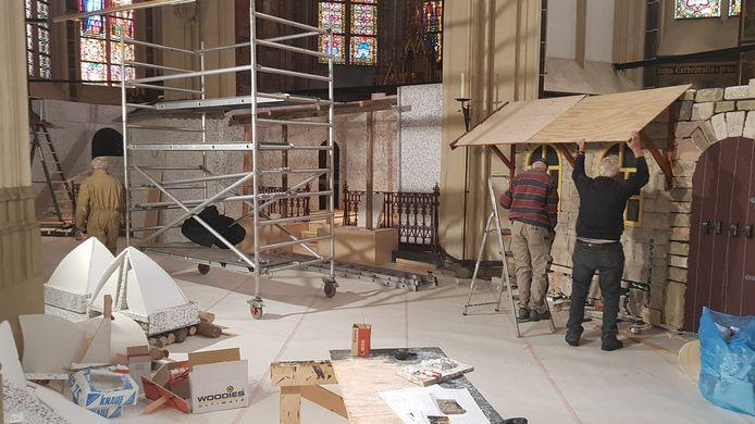 De contouren van de kerststal achter in de kathedraal worden zichtbaar.