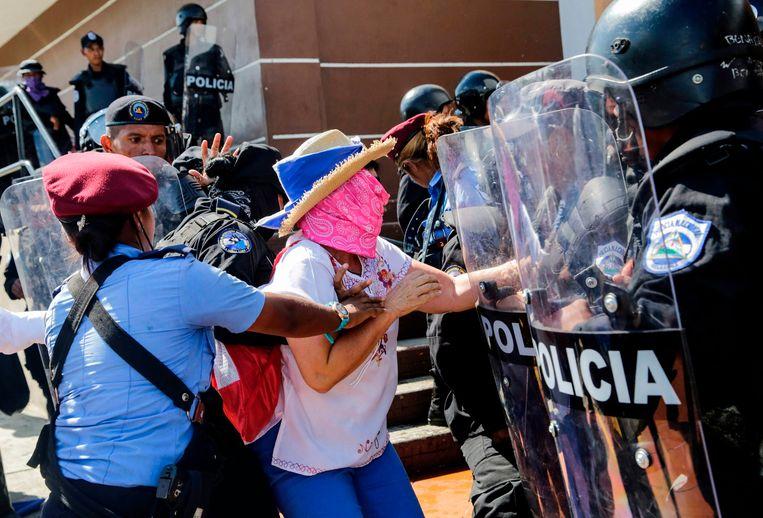 Een Nicaraguaanse vrouw wordt gearresteerd tijdens een protest tegen de regering van president Ortega, 14 oktober in Managua. Beeld AFP
