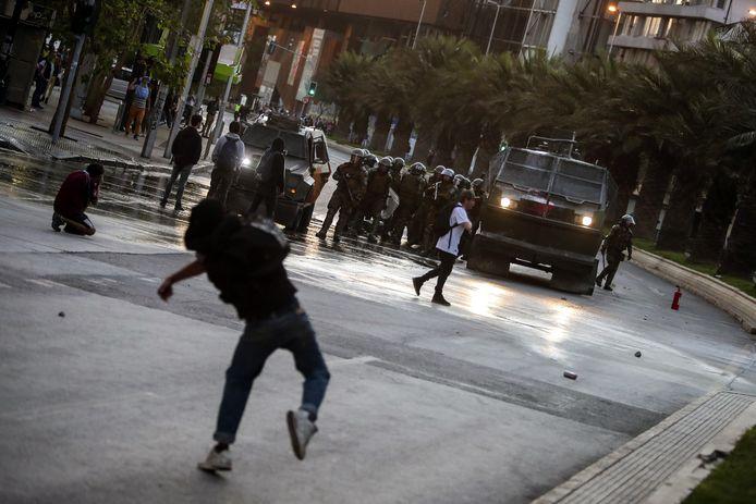 De Chileens oproerpolitie wordt bekogeld door rellende demonstranten.