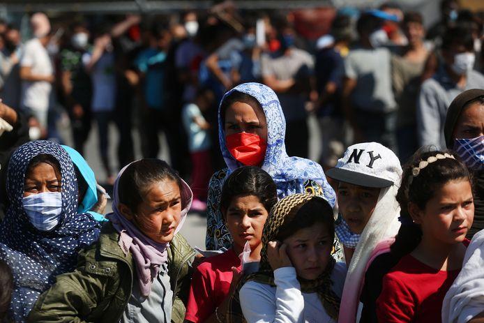 Vluchtelingen in Moria wachten op eten.