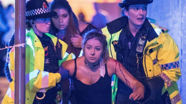 Een meisje dat gewond raakte bij de aanslag wordt ondersteund door politieagenten. Beeld Photo News