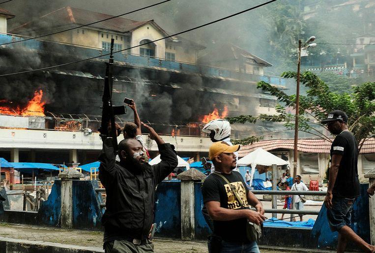 Een Papoease politieman probeert woensdag een demonstrerende menigte in Fakfak (West-Papoea) onder controle te krijgen.  Beeld EPA