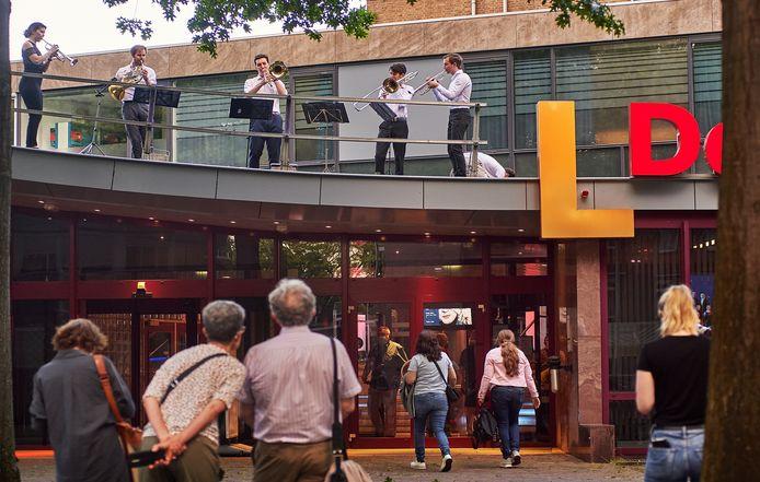 Vijf leden van het Nederlands blazersensemble heten bezoekers van theater De Lievekamp in Oss welkom vanaf het dak.