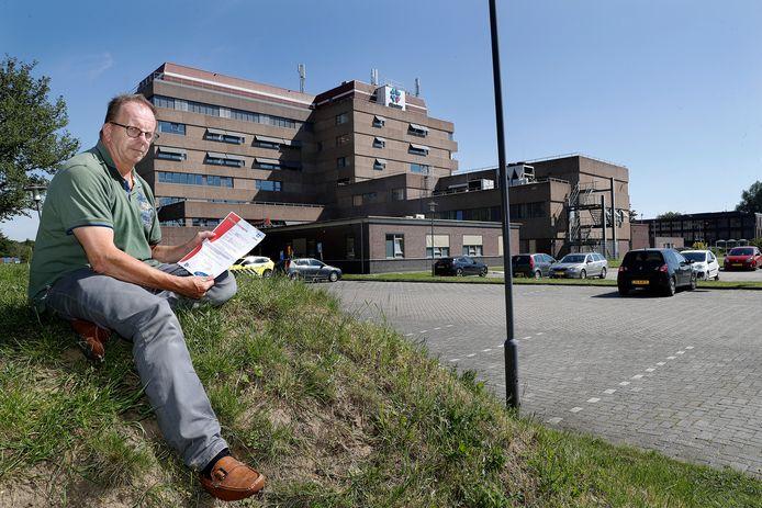 Henke Schutte met de aangetekende brief waarin hem de toegang tot alle locaties van Rijnstate wordt ontzegd. Op de achtergrond het ziekenhuis in Zevenaar.