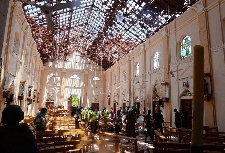 Agenten inspecteren het interieur van de kerk in Negombo.  Beeld Reuters